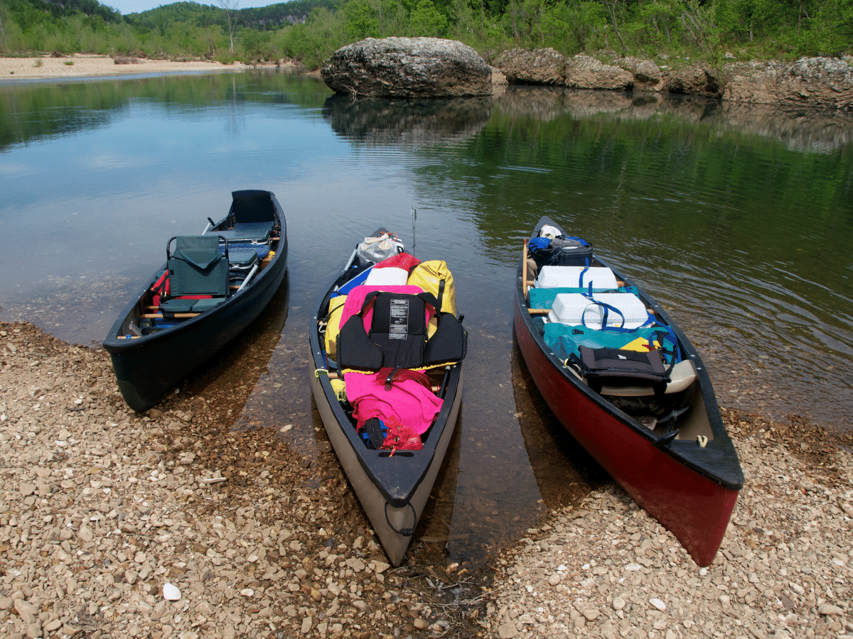 3 canoes sit on the edge of the river on calm waters