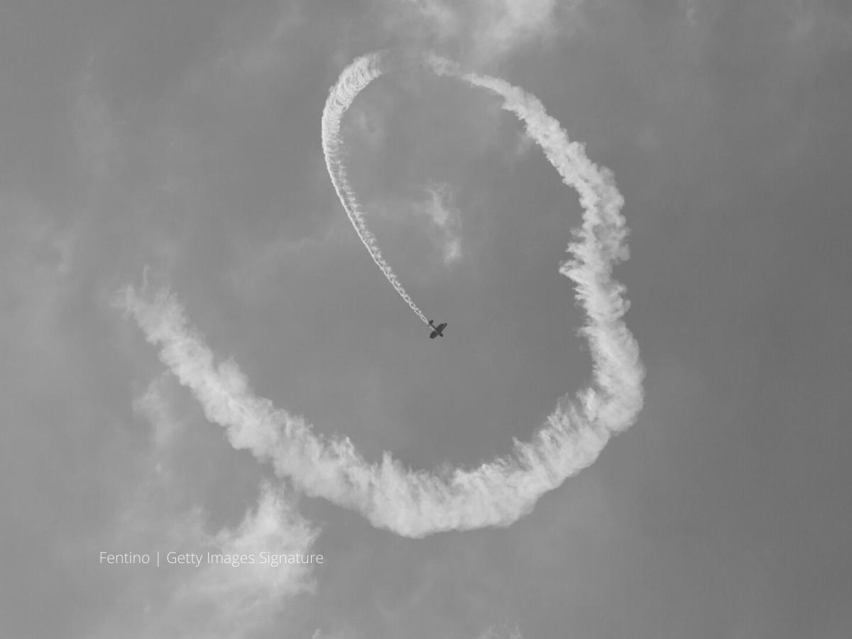 Small propeller biplane performing loop against a blue sky
