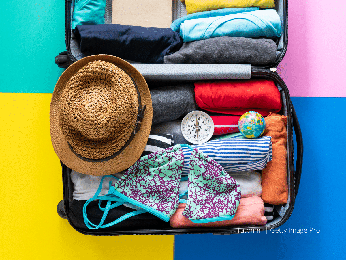Contents of a suitcase against a colorful background