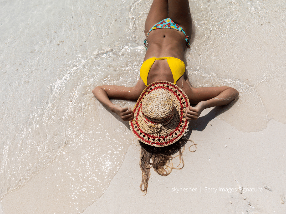 A woman lies on a sandy beach with a straw hat covering her face