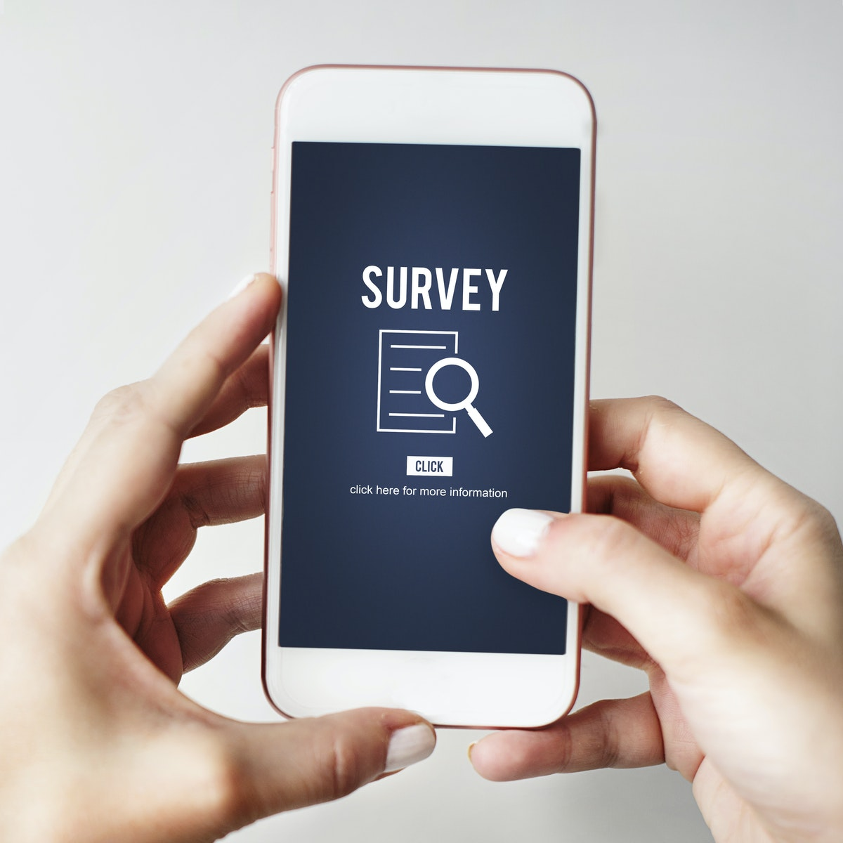 Hands holding mobile phone with depiction of a survey icon link